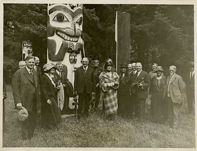 This picture was taken just before President Harding fell ill and shows the Alaskan party in front of one of the famous Totem poles at Cordova, Alaska. 31-1923-165